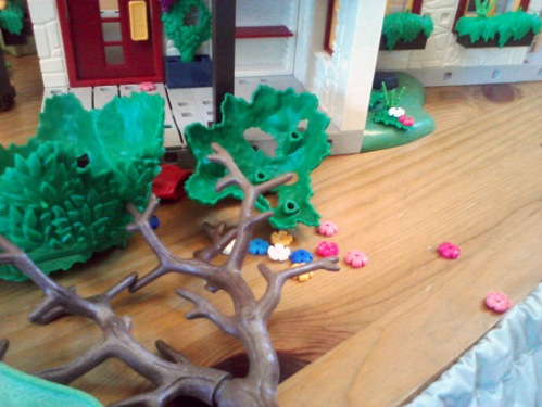 Playmobil farm hit by an earthquake - uprooted tree and damaged flowers