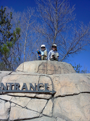 Brothers sitting on top of a rock together