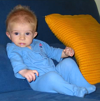 My baby boy sitting on the blue couch